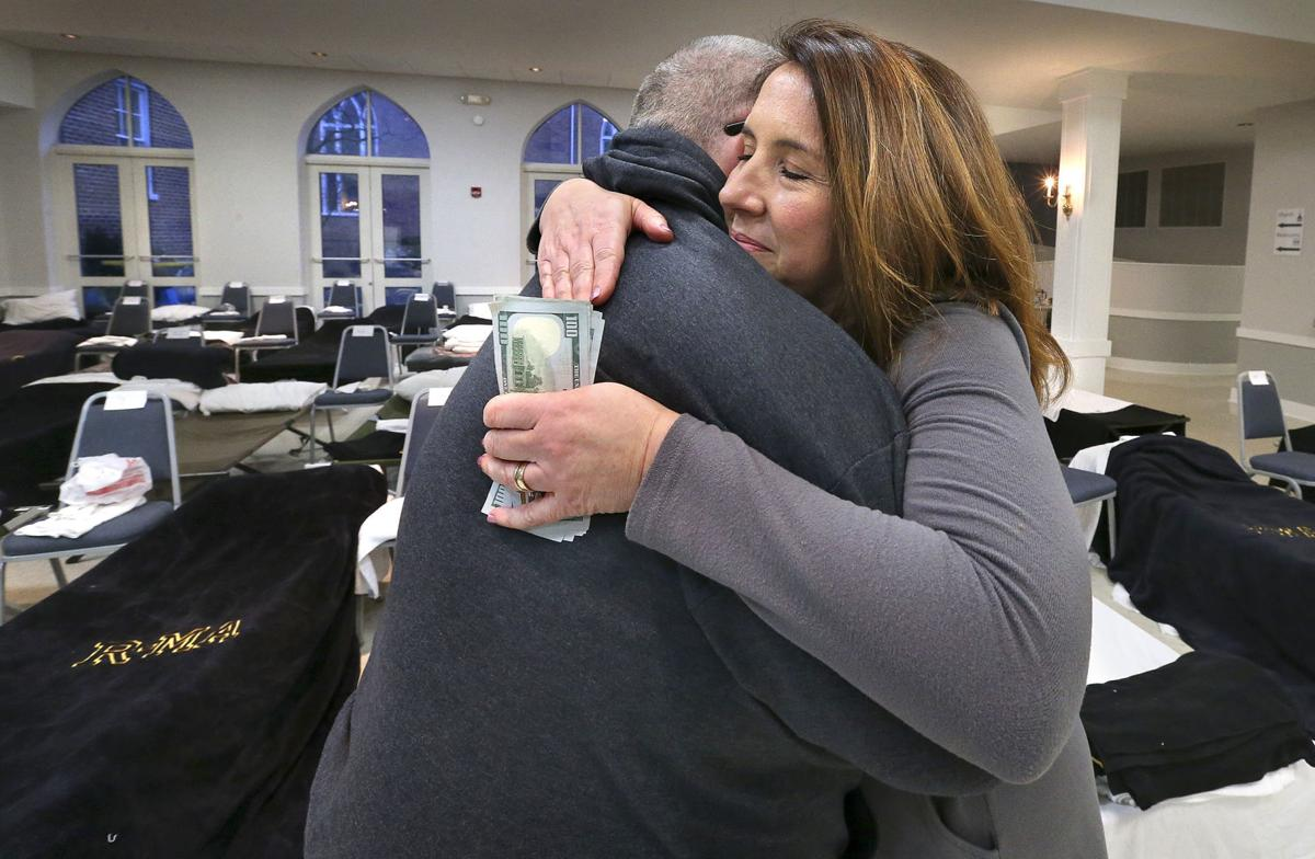 Winchester Area Temporary Thermal Shelter (WATTS) interim Executive Director Robyn Miller hugs former WATTS client Wayne Daniels as he donates $1,000 to support the program Wednesday night. Four years ago, Daniels and his girlfriend, Cherie Donivan, were homeless for a period of about four months and stayed at WATTS, which provides free overnight shelter from November to March. The program is hosted at different sites each week. This week, it is being held at Christ Episcopal Church, which is where Daniels made the donation. Photo by Jeff Taylor/The Winchester Star